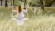 SLO MO DS Woman swinging in nature