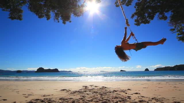 Woman swinging on rope swing by the ocean