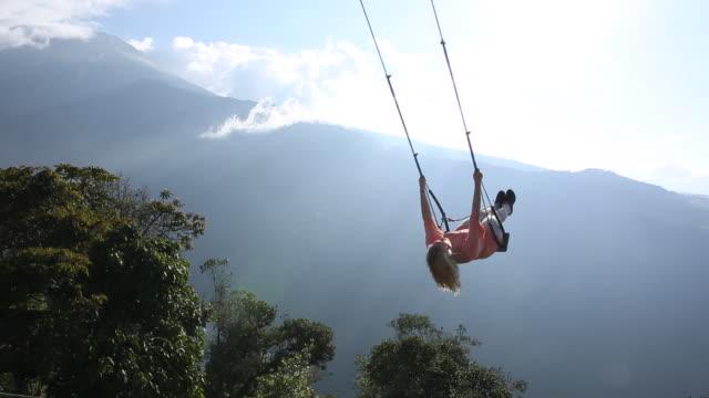 Woman swings high above valley below, towards sun