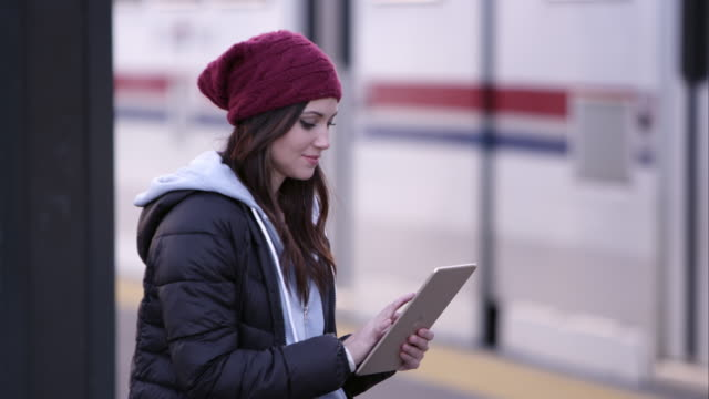 Woman swiping on tablet as she sits at transit station.