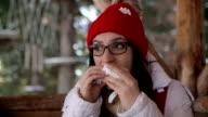 A woman takes a break in skiing, eats a sandwich