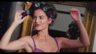 A woman takes a roller out of her hair