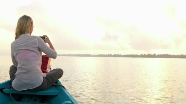 Woman takes photo from small boat at sunset