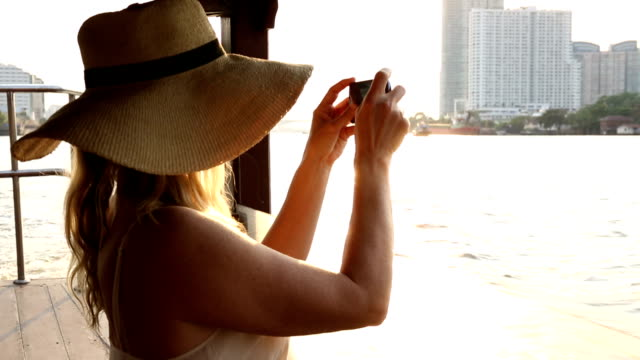 Woman takes pic of city, Chao Phraya River, from river boat