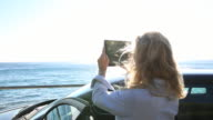 Woman takes pic of sea with digital tablet, from car door