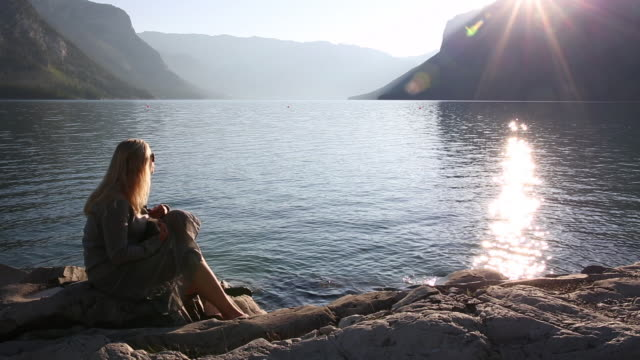 Woman takes pic with digital tablet, mountain lake, sunrise