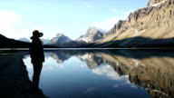 Frau nimmt Foto von mountain lake