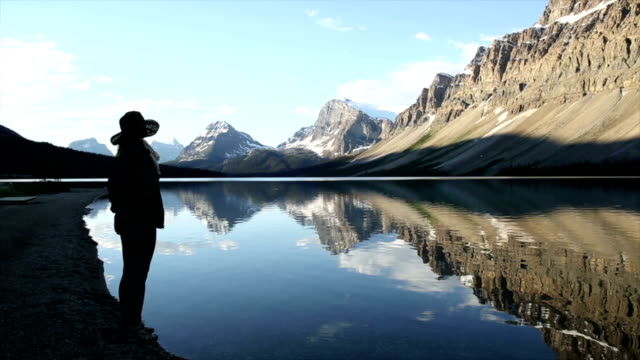 Woman takes picture of mountain lake