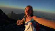 Woman takes selfie portrait on top of Table Mountain, Cape Town