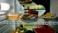 Woman takes tomatos from the fridge