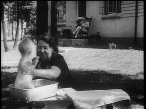 B/W 1939 woman taking baby from bath in tub + drying him off outdoors / documentary