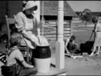 Woman taking chicken egg out of exterior nesting coop MS Woman churning butter on porch young adults w/ cauldron BG MS Woman churning milk w/ hand...