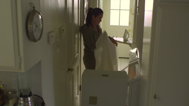 WS, PAN, Woman taking fitted sheet from dryer in laundry room, Hollywood, California, USA
