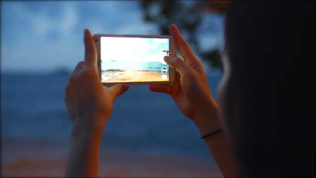 Woman taking photo at dusk