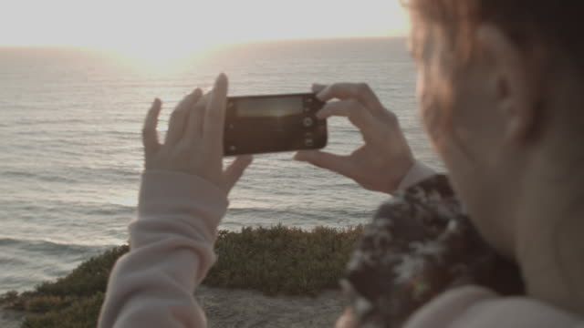Woman taking photo of sunset with mobile phone on cliff overlooking ocean