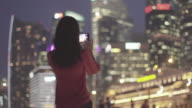 MS Woman taking photo/video of the city at night with smartphone