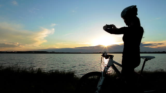 Woman taking pictures at sunset while riding the bicycle.