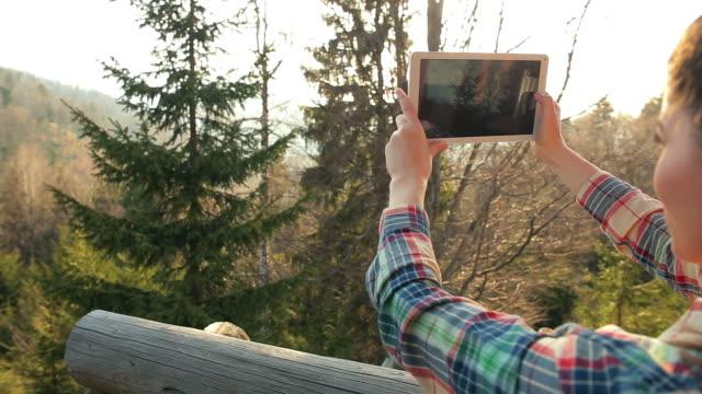Frau nimmt Fotos in Natur.