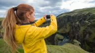Woman taking pictures of canyon