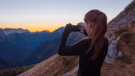 Woman taking pictures of the beautiful view with her smartphone