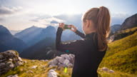 Woman taking pictures of the mountainside with smartphone