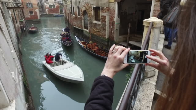 Woman taking pictures on phone in Venice