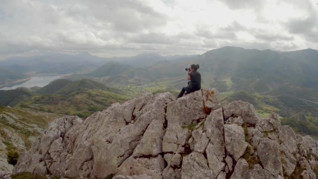 Woman taking pictures over a mountain peak