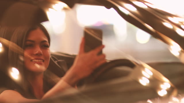 Woman taking selfie at night in car before going out