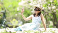 woman taking selfie with a camera in Cherry blossom garden