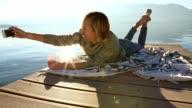 Woman taking selfies by the lake