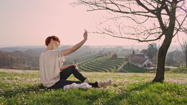 DS Woman taking selfies in grass on the hill