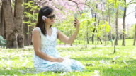 woman taking smart phone selfie in Cherry blossom garden