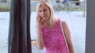 Vrouw praten over de telefoon terwijl staande op de etalage display
