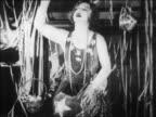 B/W 1928 woman talking + pointing to audience in nightclub floor show / newsreel