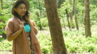 woman talking smart-phone and walking in forest