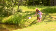 WS Woman teaching girl how to fish with net at edge of pond / Sherman, CT, USA