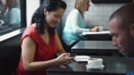 MS Woman text messaging in busy coffee shop / Seattle, Washington, USA