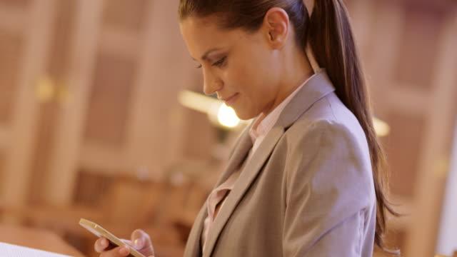 TU vrouw texting terwijl in de leeszaal van een bibliotheek