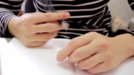 Woman thinking and playing pen while writing on notebook