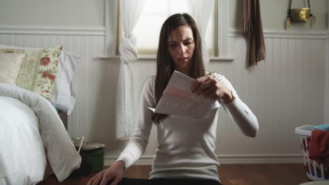 woman throwing away bills in her bedroom