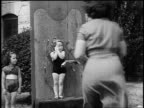 B/W 1955 REAR VIEW woman throwing knives at small girl standing against board outdoors