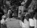 B/W 1955 REAR VIEW woman throwing knives at young girl against board outdoors / children in foreground