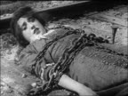 B/W 1913 woman (Mabel Normand) tied to railroad tracks with chains calling for help