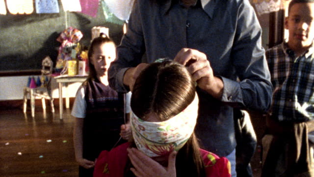 MS woman ties blindfold on girl below pinata at school birthday party /other children watch + smile