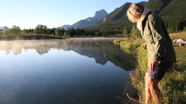 Woman touches surface of mountain lake with toe, reflection