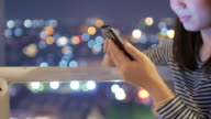 Woman touching smartphone on the rooftop with circle bokeh light of city at night time