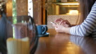 Woman touching smartphone on the table with coffee at coffee cafe