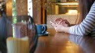 Kvinna att röra smartphone på bordet med kaffe på kaffe café