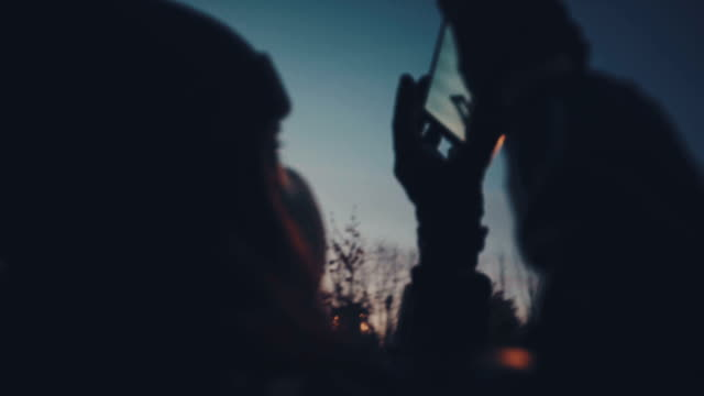 Woman tourist using smartphone take a photo of sunset