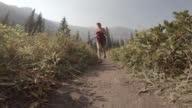Woman trail runs alpine trail